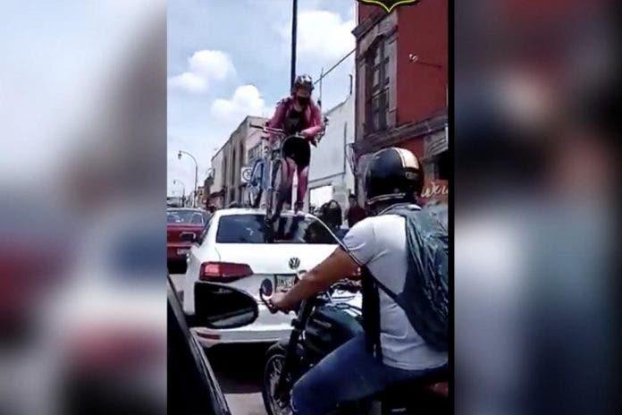 Ciclista pasa por arriba de auto